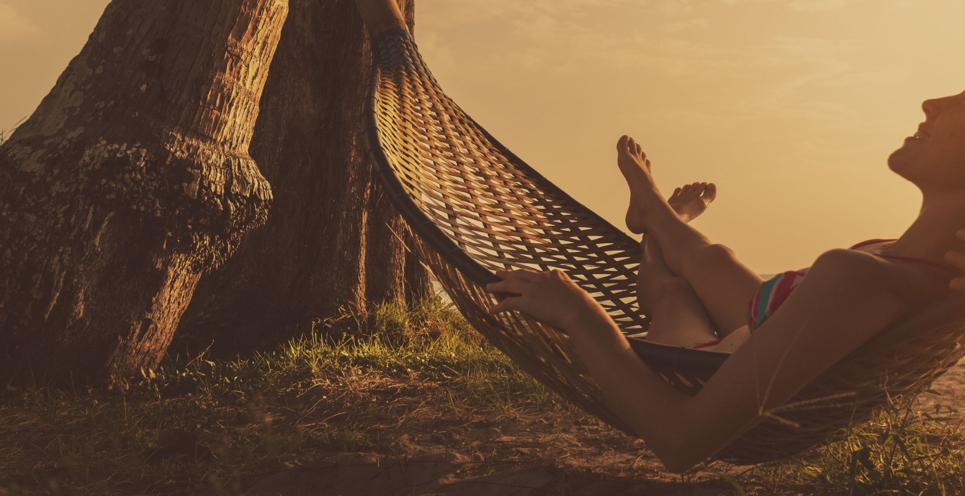 Person enjoying a hammock at sunset.